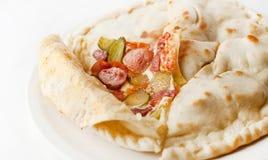 Geschlossene Pizza mit bayerischen Würsten und Essiggurken Stockbilder
