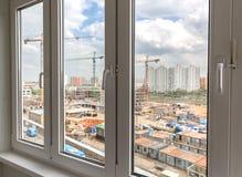 Geschlossene Plastikfenster Unscharfe Ansicht der Baustelle und des Cl Lizenzfreies Stockbild