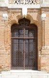 Geschlossene Schmiedeeisentür auf alter Backsteinmauer Lizenzfreie Stockfotos