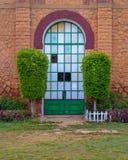 Geschlossene Schmutztür mit grünem Metallgitter gestaltet durch zwei grüne Büsche in der Steinwand der orangefarbenen Ziegelstein lizenzfreies stockfoto