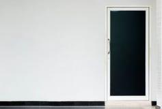 Geschlossene weiße Tür auf blauer Wand, reflektierender Boden Stockfoto