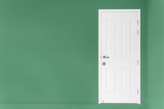 Geschlossene weiße Tür auf grüner Wand zu Hause Stockfotografie