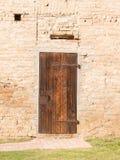 Geschlossene Weinleseholztür auf Backsteinmauer lizenzfreie stockbilder