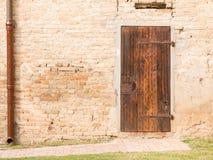 Geschlossene Weinleseholztür auf Backsteinmauer stockfoto