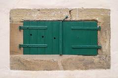 Geschlossener grüner Fensterfensterladen auf einem Kellerfenster Stockbild