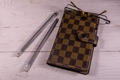 Geschlossener Notizblock, Bleistifte und Brillen auf Holztisch Beschneidungspfad eingeschlossen Lizenzfreie Stockbilder