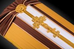 Geschlossener Sarg bedeckt mit dem braunen und beige Stoff verziert mit Kirchengoldkreuz auf grauem Luxushintergrund Nahaufnahme Stockfoto