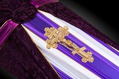 Geschlossener Sarg bedeckt mit dem purpurroten und weißen Stoff verziert mit Kirchengoldkreuz auf grauem Luxushintergrund Nahaufn Stockfotografie