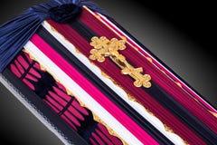 Geschlossener Sarg bedeckt mit dem rosa und blauen Stoff verziert mit Kirchengoldkreuz auf grauem Luxushintergrund Nahaufnahme Stockfoto