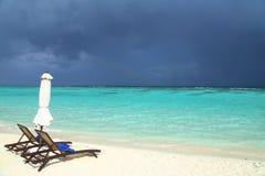 Geschlossener weißer Strandschirm und Stühle Ruhiger Meerblick Abstrakte Ferien, Feiertage und Sommerbild Regen lizenzfreie stockfotografie