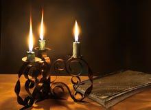 Geschlossenes altes Buch und drei brennende Kerzen im Kerzenständer Stockfoto