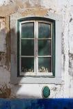 Geschlossenes altes Fenster mit kleinen Spielwaren Stockfotos