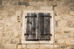 Geschlossenes altes hölzernes Fenster auf Steinwand lizenzfreie stockfotos