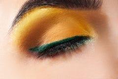Geschlossenes Frauenauge mit gelbem Make-up und grünem Streifen Lizenzfreie Stockbilder
