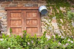 Geschlossenes hölzernes Fenster auf gealterter Backsteinmauer Stockfoto