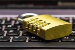 Geschlossenes Kombinationsvorhängeschloß auf einer Laptoptastatur, die Datensicherheit symbolisiert Lizenzfreie Stockbilder