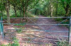 Geschlossenes Metalltor, das den Eingang zu einem Waldweg in blockiert Lizenzfreie Stockfotos