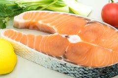 Geschlossenes-oben rohes Lachssteak mit Gemüse auf Platten-, Lebensmittel- und Gemüsekonzept Stockfotografie