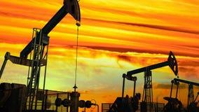 Geschlungene Bewegung entlang Ölpumpensteckfassungen gegen Dämmerung stock video
