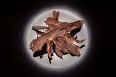 Geschmackvoll, knusperig, Fleisch, geräucherter, klarer Imbiss auf einem schwarzen Hintergrund lizenzfreies stockbild