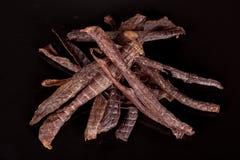 Geschmackvoll, knusperig, Fleisch, geräucherter, klarer Imbiss auf einem schwarzen Hintergrund lizenzfreie stockfotografie