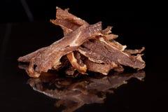 Geschmackvoll, knusperig, Fleisch, geräucherter, klarer Imbiss auf einem schwarzen Hintergrund lizenzfreie stockfotos
