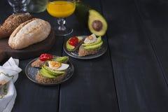 Geschmackvoll und Saft, Sandwich mit Avocado, Tomate und poschiertes Ei auf hölzernem hackendem Brett, Abschluss oben, selektiver stockfoto