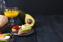 Geschmackvoll und Saft, Sandwich mit Avocado, Tomate und poschiertes Ei auf hölzernem hackendem Brett, Abschluss oben, selektiver lizenzfreies stockbild
