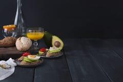 Geschmackvoll und Saft, Sandwich mit Avocado, Tomate und poschiertes Ei auf hölzernem hackendem Brett, Abschluss oben, selektiver lizenzfreie stockfotos