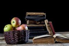 Geschmackvolle Äpfel im Korb auf Küchentisch Lüge der alten Bücher nahe bei a Stockbild