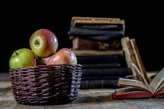 Geschmackvolle Äpfel im Korb auf Küchentisch Lüge der alten Bücher nahe bei a Stockfoto