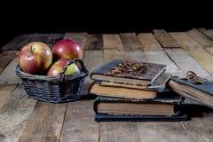 Geschmackvolle Äpfel im Korb auf Küchentisch Lüge der alten Bücher nahe bei a Stockfotografie