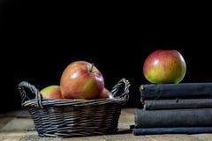 Geschmackvolle Äpfel im Korb auf Küchentisch Lüge der alten Bücher nahe bei a Lizenzfreie Stockfotografie