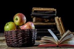 Geschmackvolle Äpfel im Korb auf Küchentisch Lüge der alten Bücher nahe bei a Lizenzfreies Stockfoto