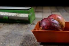 Geschmackvolle Äpfel und alte Küchenskalen auf einem Holztisch Küche s Stockfotografie