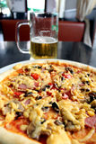 Geschmackvolle appetitanregende Pizza und Glas Bier Lizenzfreie Stockfotos
