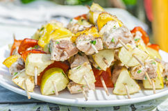 Geschmackvolle Aufsteckspindeln von frischen Fischen mit Gemüse und von Äpfeln auf einem hölzernen Kebab Stockfotografie