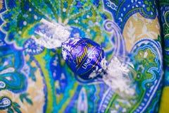 Geschmackvolle blaue Schokolade Lindt Lindor über silk Hintergrund Stockbilder