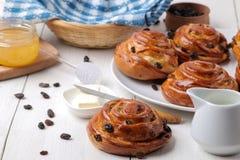 Geschmackvolle Brötchen mit Rosinen mit Butter, Milch und Honig auf einem weißen hölzernen Hintergrund Frische Bäckerei Frühstück lizenzfreies stockfoto