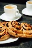 Geschmackvolle Brezeln und zwei Tassen Tee auf dunklem Holztisch Stockfoto