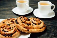 Geschmackvolle Brezeln und zwei Tassen Tee auf dunklem Holztisch Stockfotografie