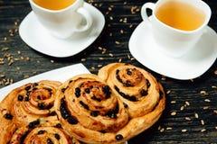 Geschmackvolle Brezeln und zwei Tassen Tee auf dunklem Holztisch Lizenzfreies Stockfoto