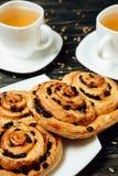 Geschmackvolle Brezeln und zwei Tassen Tee auf dunklem Holztisch Lizenzfreies Stockbild