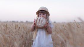 Geschmackvolle Brotkindheit, kleine nette Kindermädchenbisse backte frisch das Brot und Lächeln, die es auf dem goldenen Kornweiz stock footage