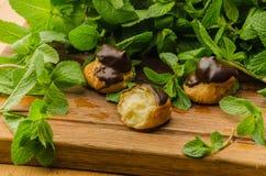 Geschmackvolle Eclairs bedeckt mit chocolade auf hölzernem Brett Stockfoto