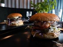 Geschmackvolle enorme Burger in einem Restaurant - an einem Tisch lizenzfreies stockfoto