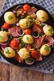 Geschmackvolle Frühkartoffeln mit Draufsicht der Zwiebel, der Tomate und des Speckes Lizenzfreie Stockbilder