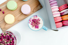 Geschmackvolle französische macarons und eine Schale Cappuccino mit den Rosenblumenblättern Lizenzfreie Stockbilder