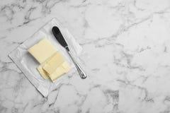Geschmackvolle frische Butter und Messer auf Tabelle Stockfotos