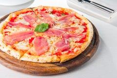 Geschmackvolle ganze italienische Pizza überstieg mit dünn geschnittenem Prosciuttoschinken auf der gedienten Restauranttabelle Stockfotografie